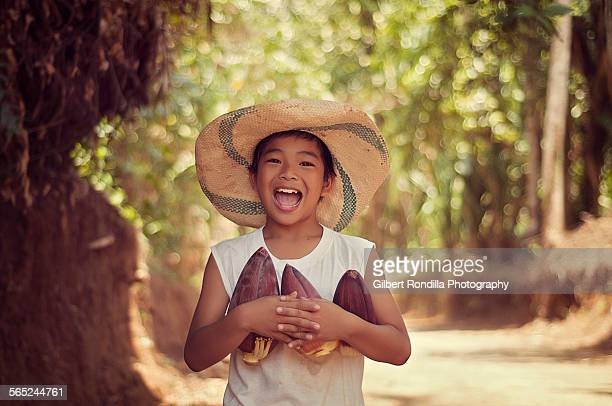farm boy holding banana blossoms - filipino farmer stock photos and pictures