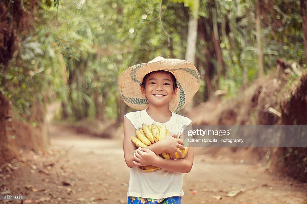 Farm boy holding bananas : Stock Photo