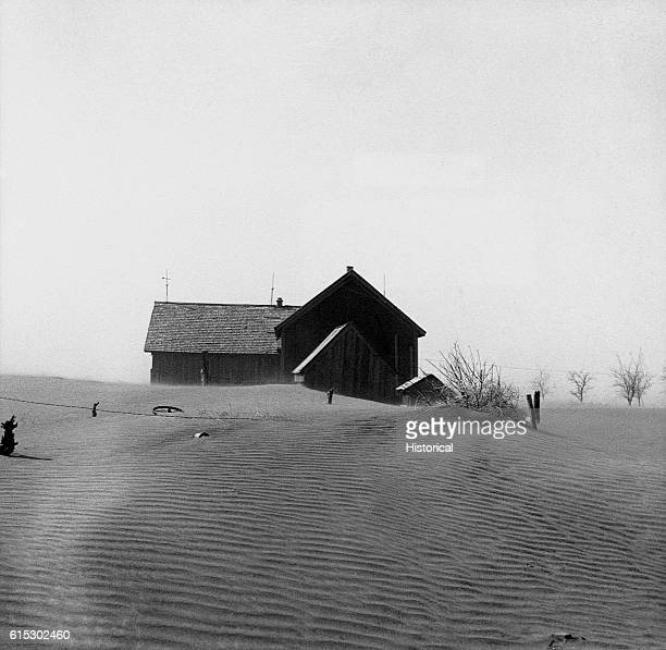A farm covered in loose soil after a dust storm Cimarron County Oklahoma April 1936