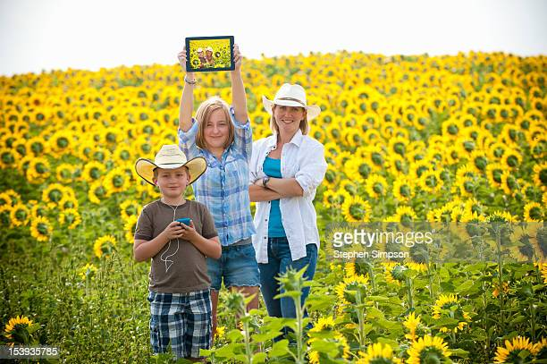 farm family with technology in field of sunflowers