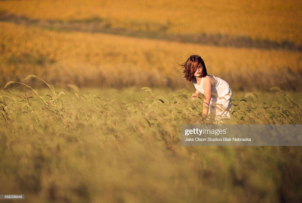 Farm girl in windy grass : Stock Photo