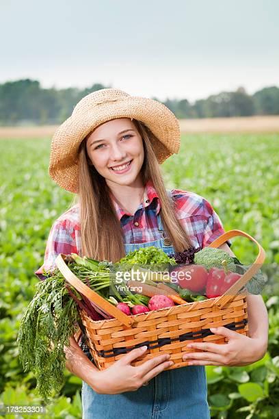 Farm Mädchen mit Korb mit frisch geernteten Produkte Gemüse, Vt