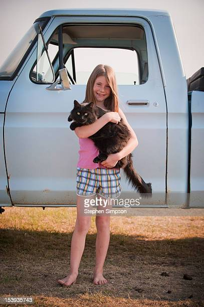 farm girl with her pet cat and pick up truck