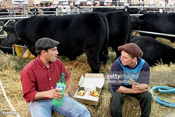 Farm hands take a break to eat pasties at an AnGus box during the 119th Rural Expo 01 August 2005 in Buenos Aires AFP PHOTO DANIEL GARCIA Peones...