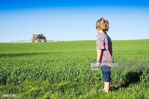 Farm kid looking at a crop sprayer