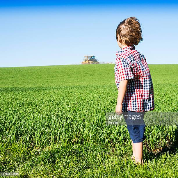 Farm kid watching a crop sprayer.
