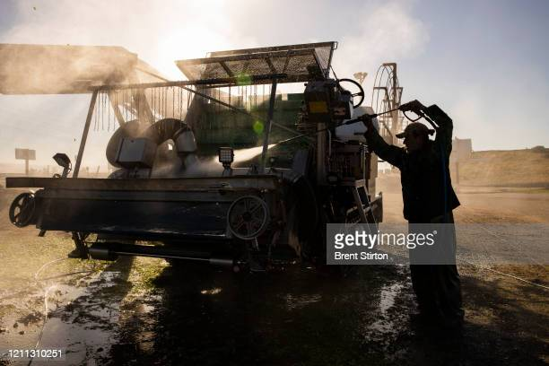 A farm laborer with Fresh Harvest hoses down a harvesting machine on April 28 2020 in Greenfield California Fresh Harvest is the one of the largest...
