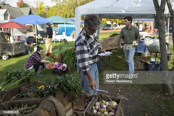 Farm owner Dominic Palumbo 56 years marks prices on his organically grown vegetables October 6 2012 at the weekly farmers' market in Millerton New...