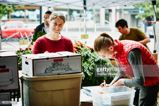 Farm owner setting up market stand with employee