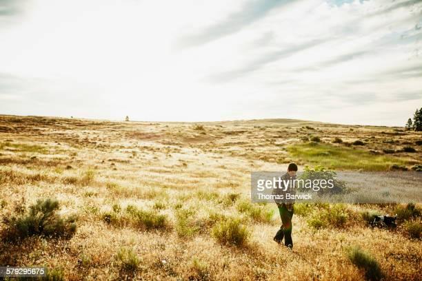 Farm owner walking with dog through field on farm