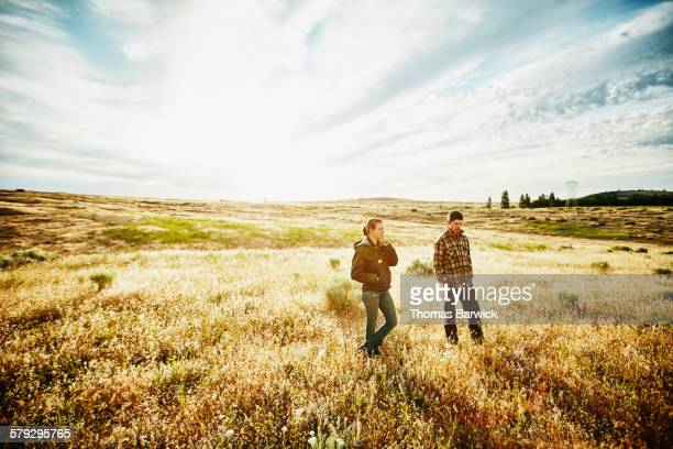 Farm owners in discussion in field at sunrise