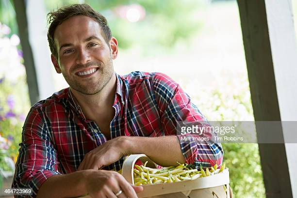 A farm stand with fresh organic vegetables and fruit.  A man holding a full basket of beans.