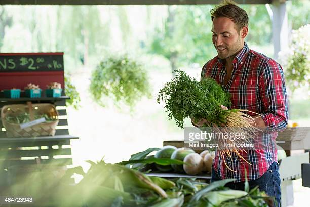 A farm stand with fresh organic vegetables and fruit.  A man holding bunches of carrots.