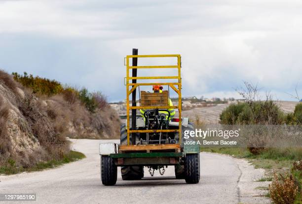 farm tractor forklift next to a field laden with boxes of oranges driving on the road. - fruit laden trees stock pictures, royalty-free photos & images