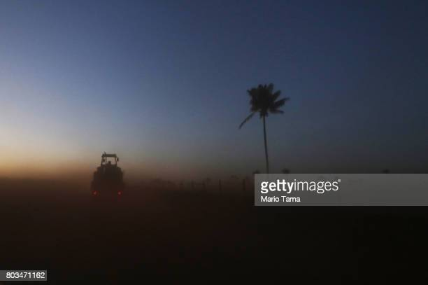 A farm tractor is towed on a truck kicking up Amazon soil as it travels in a deforested section of the Amazon rainforest on June 28 2017 near...