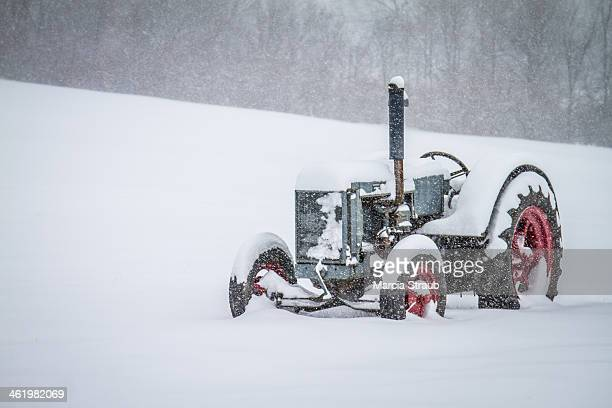 CONTENT] A farm tractor parked in the field in Illinois during a winter snow storm