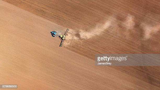 Farm tractor planting and cultivating spring fields, aerial view