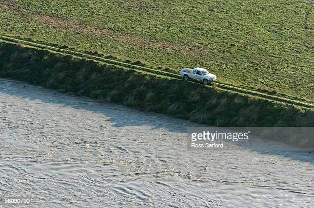 A farm truck skirts the flood bank above the swollen Rangitikei River near Tangimoana in the Manawatu New Zealand Thursday July 01 2004 The area was...