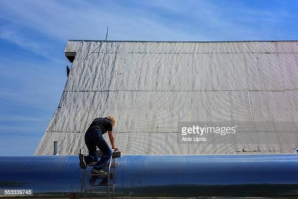Farm wife on checks milk tanker on dairy farm
