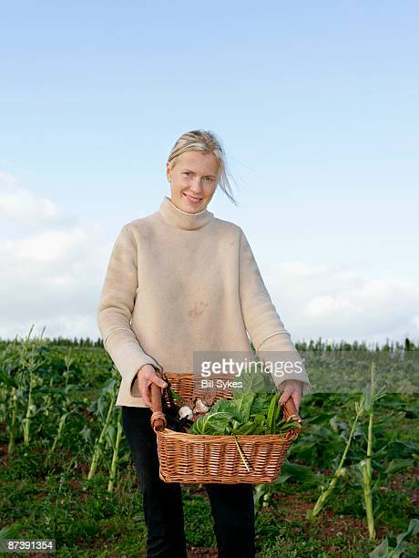 farm worker carries basket of veg