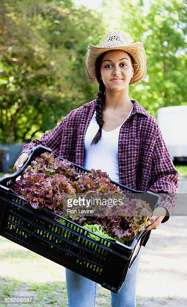 Farm worker with container of lettuce, portrait
