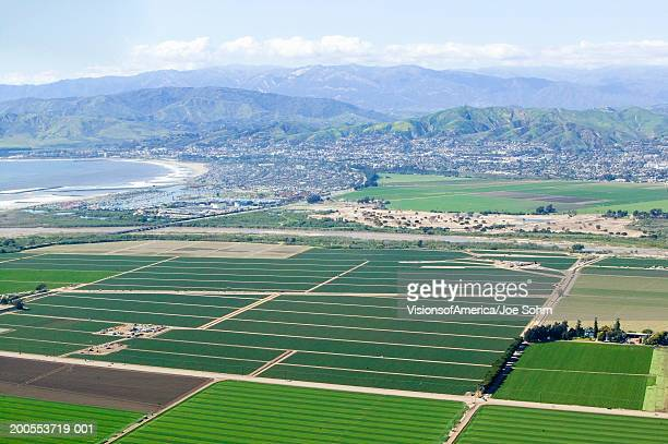 Farmed fields with ocean and town in background, aerial view