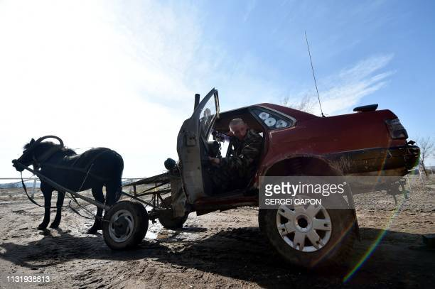 TOPSHOT Farmer Alexei Usikov gets into his horsepulled cart made from an old Audi 80 car in the village of Slabodka some 232 km east of Minsk on...