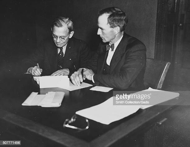 A farmer and a banker both in suits signing farm debt adjustment papers Champaign Illinois 1936 From the New York Public Library
