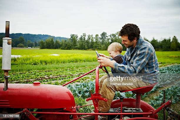 Farmer and baby boy sitting on tractor in field