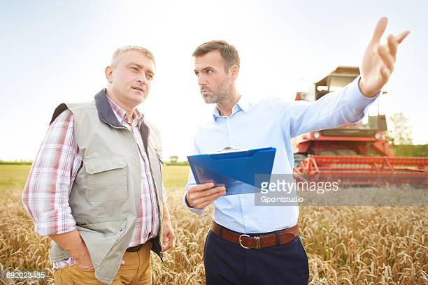 Farmer and businessman in wheat field holding clipboard looking away