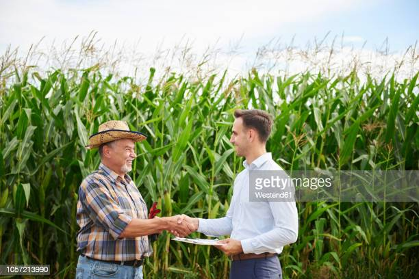 Farmer and businessman shaking hands at the cornfield