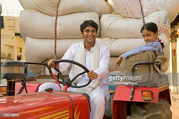 A farmer and his daughter on the tractor