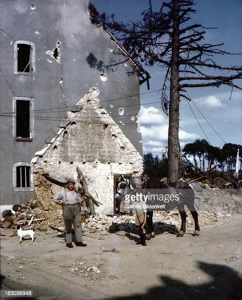 A farmer and his son in front of their damaged house during the Allied invasion of France Normandy July 1944 Bombing of German positions has caused...
