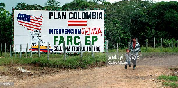 A farmer and his son walk pass a Revolutionary Armed Forces of Colombia billboard October 2 2000 outside San Vicente del Caguan Caqueta Colombia The...