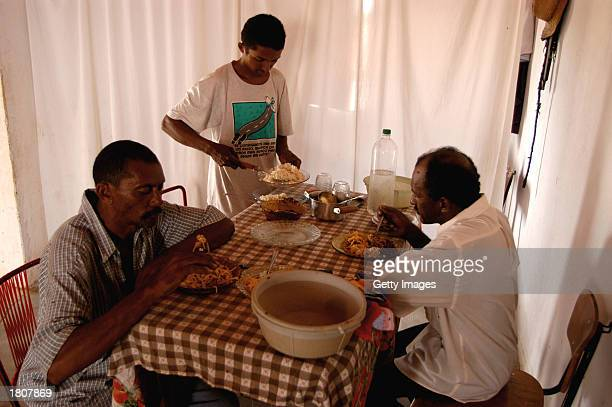 Farmer and honey producer Francelino Diocleciano Souza has lunch with his son and a friend at his house February 16 2003 in Lagoa da Caridade Brazil...