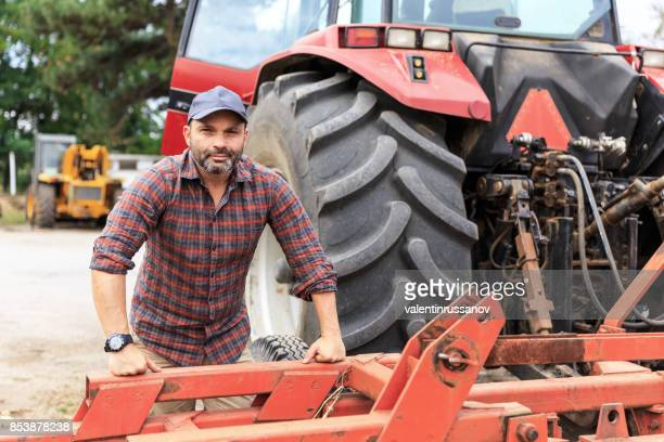 farmer and red tractor - tractor stock pictures, royalty-free photos & images