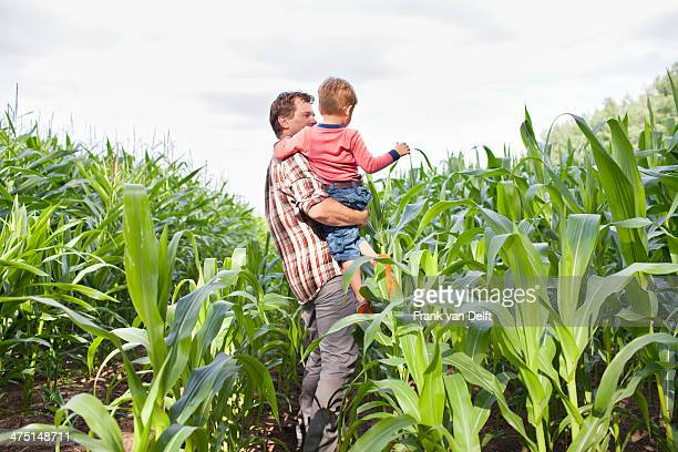 Farmer and son in field of crops
