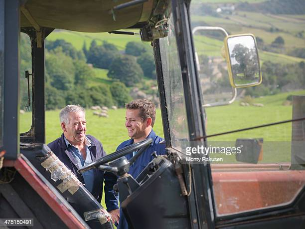 Farmer and son talking next to tractor in field