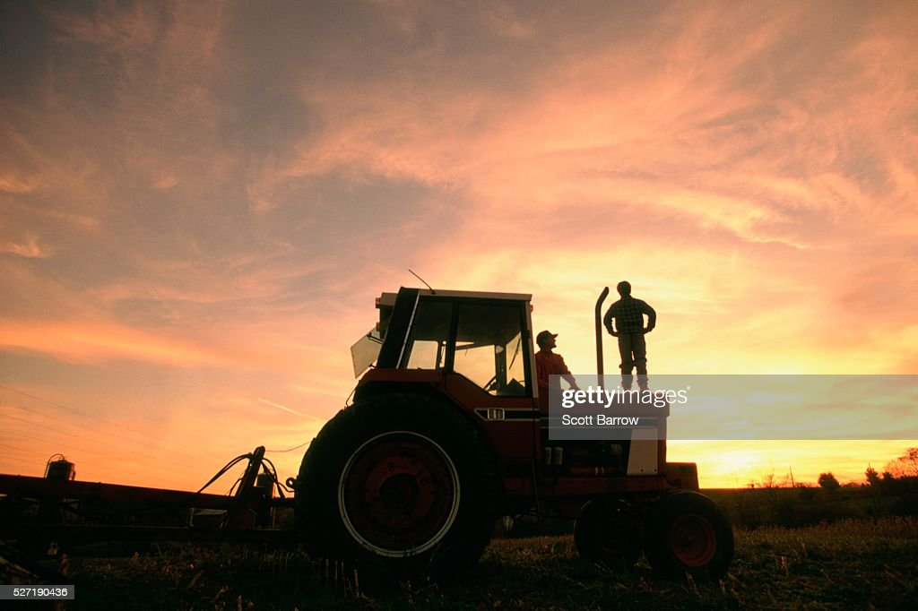Farmer and son watching the sunset : Photo