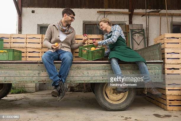 Farmer and worker taking rest and examine the apples harvest, Bavaria ,Germany