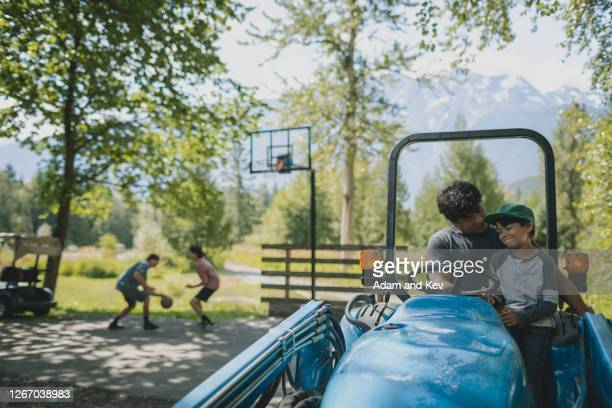 Farmer and young son drive tractor while brothers take a break