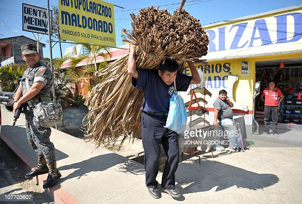 A farmer carries maguey leaves while a Guatemalan soldier stands guard in the streets of Coban Alta Verapaz 220km north of Guatemala City on December...