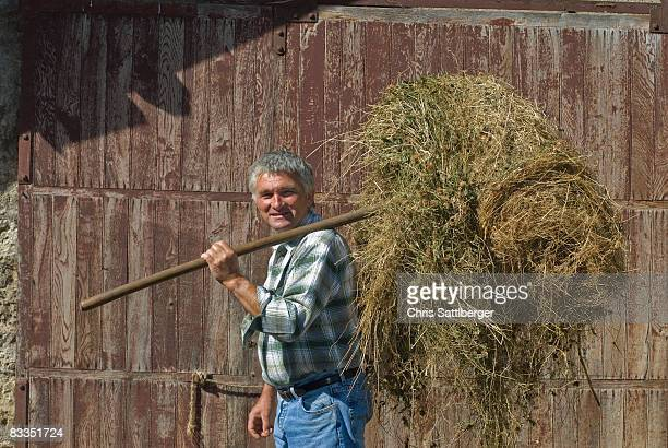 farmer carrying a forkful of hay