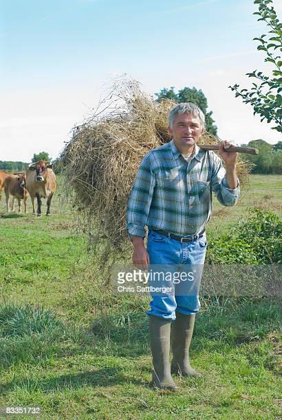 farmer carrying hay in field