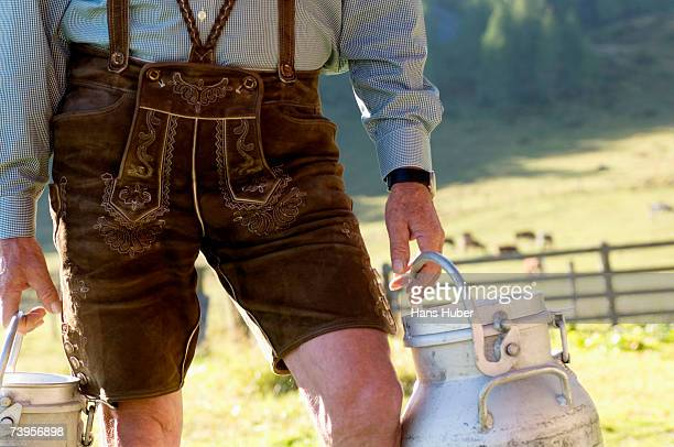 Farmer carrying milk cans, mid section, close-up