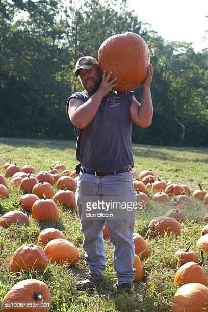 Farmer carrying pumpkin in farm, smiling, portrait