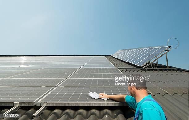 Farmer cleaning solar panels on barn roof, Waldfeucht-Bocket, Germany