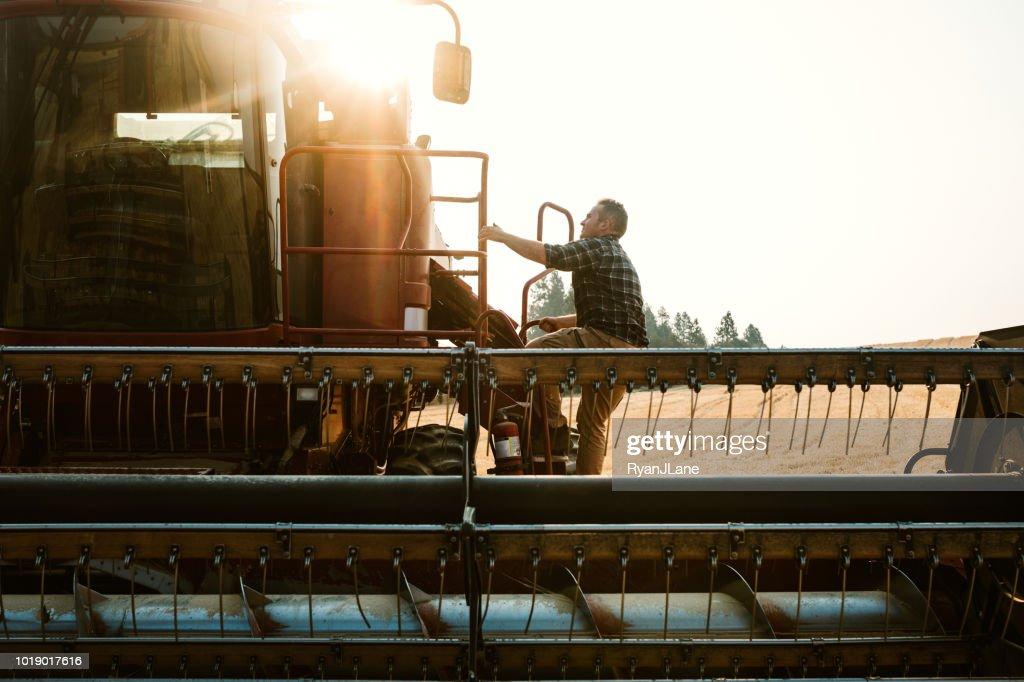 Farmer Climbing In To Combine Harvester In Idaho Wheat Field : Stock Photo