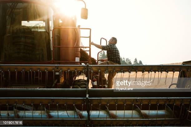 Farmer Climbing In To Combine Harvester In Idaho Wheat Field