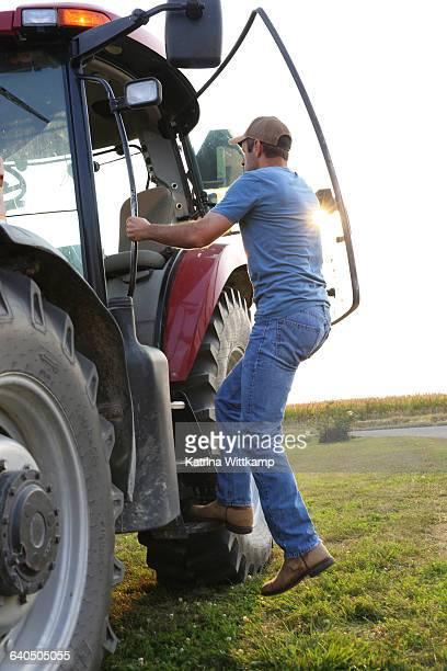 Farmer climbing into tractor